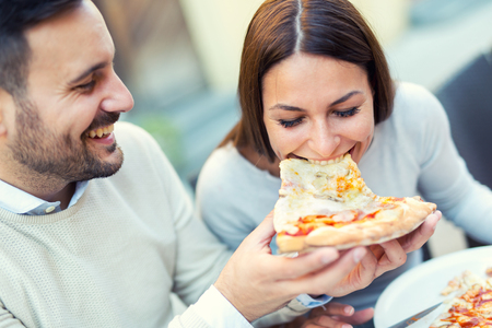 Couple eating pizza snack outdoors.They are sharing pizza and eating. Foto de archivo