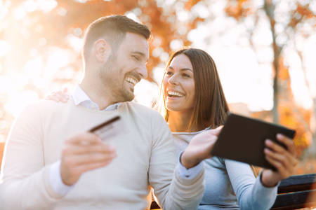 Cheerful young couple sitting on a park bench and uses a digital tablet for online shopping Banco de Imagens - 88637981
