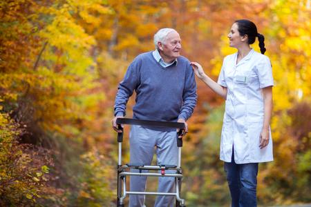 Verpleegster die de bejaarde hogere mens helpen. Hogere mens die een leurder met verzorger met behulp van openlucht