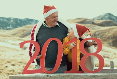 2018 sign in the hands of a senior caucasian man and little boy outdoor. New Year concept.