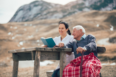 Smiling nurse reading book to senior man outdoor