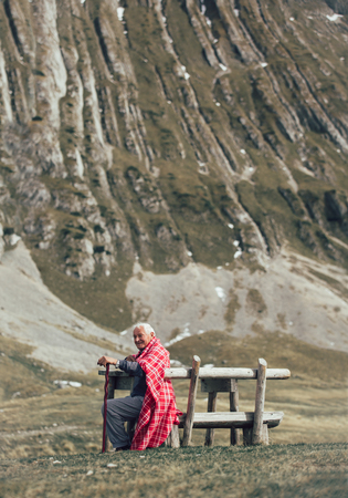 Lonely senior man sitting on bench on his hands folded on the cane and being absorbed into his thoughts. He enjoyes on the fresh air on the mountain Stock Photo