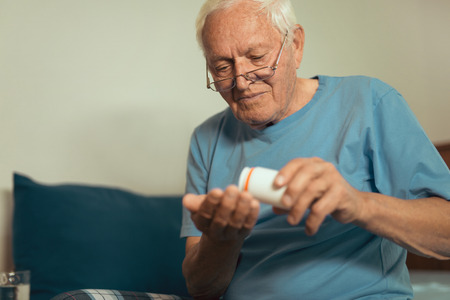 Senior Man Sitting On Bed At Home Taking Medication Stock Photo