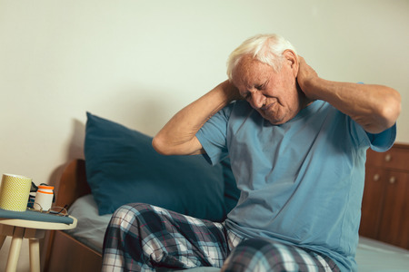 Senior man in pajamas feeling pain in his neck seated on a bed