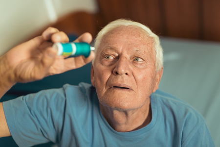 Senior man using eye drops, prevention of eye diseases