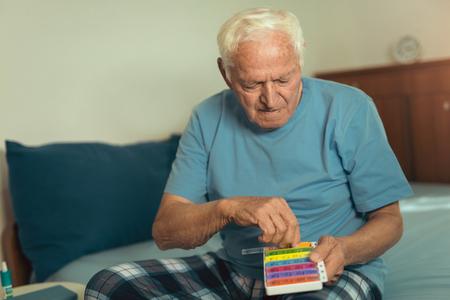 薬を服用して自宅でベッドに座っているシニア男性