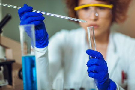 Young female scientist in protective glasses and gloves dropping a liquid substance into the test tube with a long glass pipette in the scientific chemical laboratory Stock Photo