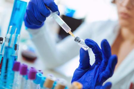 Lekarz przygotowuje strzykawkę z lekiem na szczepienie.