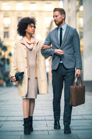 Businesspeople commuting and walking in busy city together