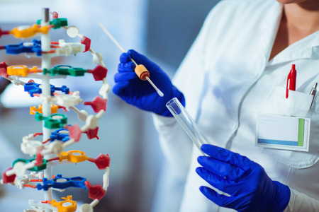 Woman collects forensic DNA sample stick in laboratory Stock Photo