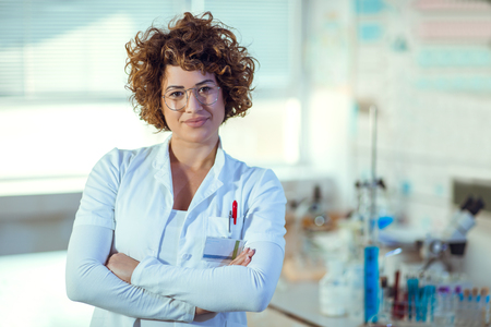 Experienced female scientist  in laboratory looking at camera.