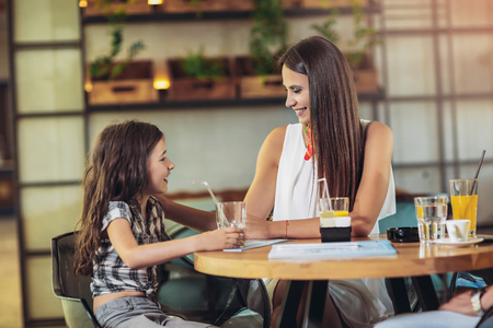 Mother and daughter having great time in a restaurant
