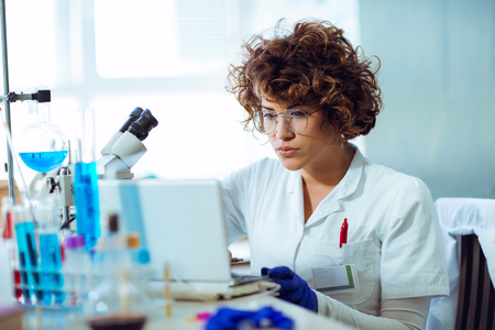Portrait of confident female scientist working on laptop in chemical laboratory Stock Photo