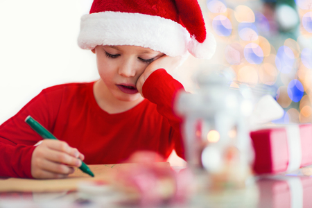 Boy writing letter to Santa Claus in red hat near the Christmas tree