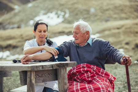 Nurse measuring old patients blood pressure outdoor