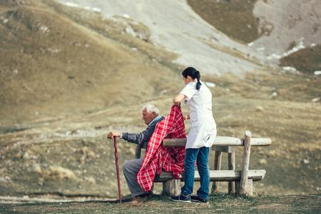 Nurse helping elderly senior man to walk on frash air outdoor.