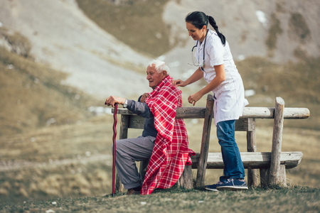 Nurse helping elderly senior man to walk on frash air outdoor.