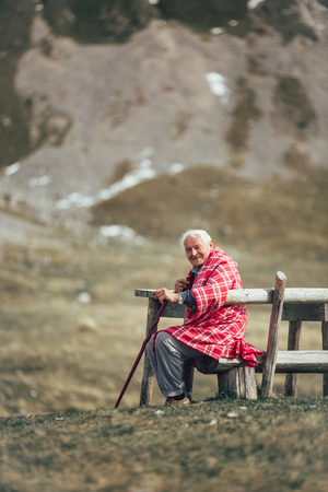 Lonely senior man sitting on bench being absorbed into his thoughts. He enjoyed on the fresh air on the mountain