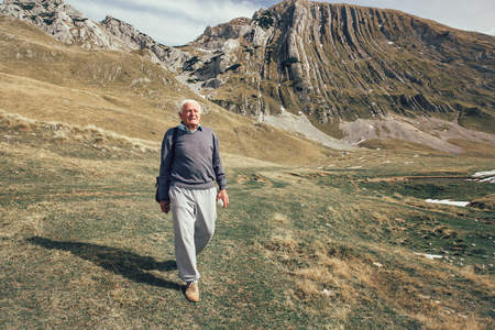 Serious senior man with gray hair on the mountains road 스톡 콘텐츠