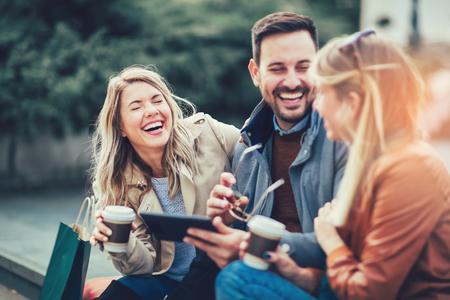 Gruppe lächelnder Freunde mit digitalem Tablett im Freien Standard-Bild