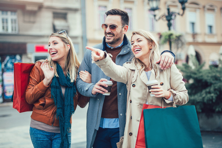 consumerism: Group Of Friends Walking Along Street With Shopping Bags Stock Photo