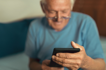 デジタルタブレットを使用してシニアの男性。自宅でポータブルコンピュータを使用して驚いた成熟した男性