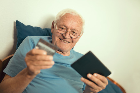 Senior man with credit card for on line banking or shopping