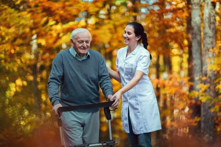Infirmière aidant un homme âgé âgé. Senior homme à l'aide d'une marchette avec soignant en plein air Banque d'images - 90101925