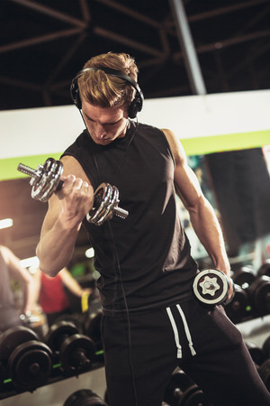 Portrait of a young muscular man exercising with dumbbells in the gym.