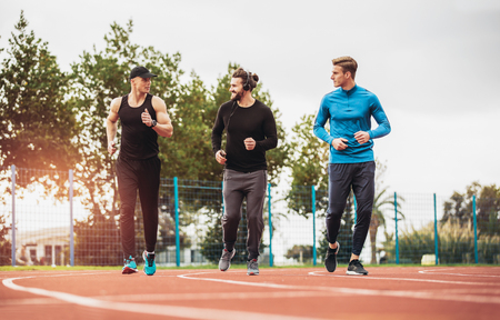 Young athletes practicing a run on athletics stadium track. Stock Photo