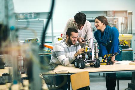 워크샵에서 테스트를 위해 로봇을 준비하는 로봇 공학의 어린 학생들