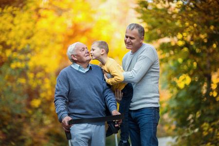 高齢者は大人の息子と公園に散歩に出て孫を父します。 写真素材