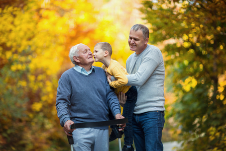 Elderly father adult son and grandson out for a walk in the park. Stock Photo