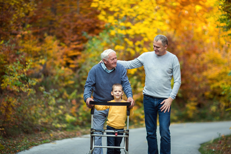 高齢の父親大人の息子と孫が公園を散歩に出かける。