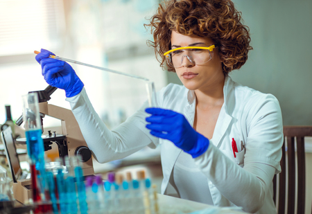 Young female scientist in protective glasses and gloves preparing a liquid substance for test tube with a long glass pipette in the scientific chemical laboratory