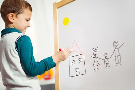 Schattige kleine jongen tekenen op wit bord met viltstift en glimlachen. Vroeg onderwijsconcept Stockfoto