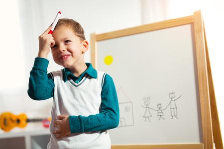 フェルト ペンと笑顔でホワイト ボードに描くかわいい男の子。初期の教育概念