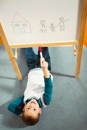 Cute little boy drawing on white board with felt pen and smiling. Early education concept. Photo from above