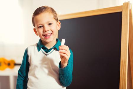 Kleine jongen die met krijt voor schoolbord. Vroeg onderwijsconcept Stockfoto