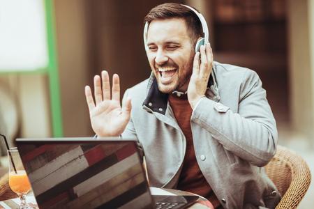 Overjoyed man talking through the Internet outdoor