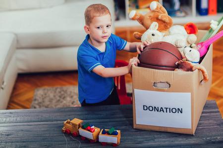 소년 기부 상자에 물건을 가득 기부에 대한 복용