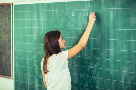 Happy schoolchild writing on blackboard with chalk Reklamní fotografie