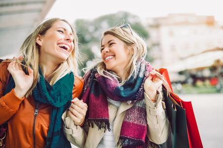 Happy friends shopping. Two beautiful young women enjoying shopping in the city. Foto de archivo