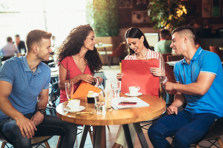 Group of young people meeting in a cafe after shopping