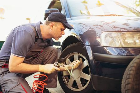 자동차 타이어 피팅 및 균형 조정에서 정비공 수리공 스톡 콘텐츠 - 91378500