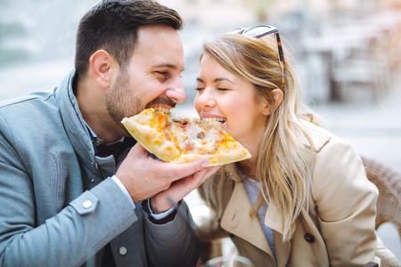 Couple eating pizza snack outdoors and smiling