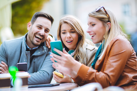 Group of three friends using phone in outdoor cafe on sunny day
