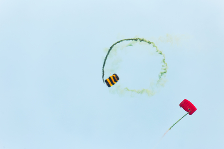 Two Parachutists fly to the blue sky