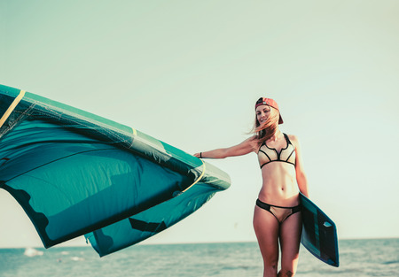 Pretty smiling Caucasian woman kitesurfer walking on the beach with her board Stock Photo