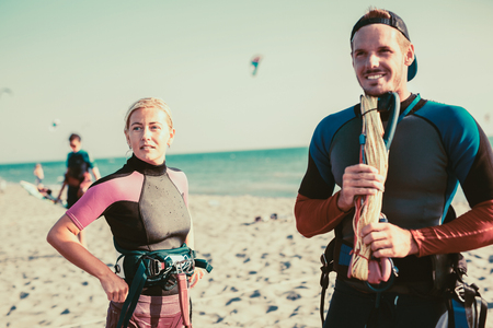 Pretty smiling Caucasian woman kitesurfer enjoying summertime on sandy beach with her boyfriend.
